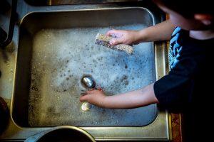 Ein Kind putzt Haushaltsprodukte